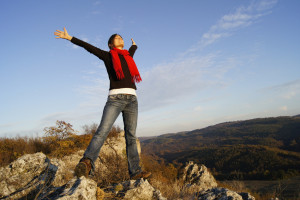 Young girl stretching her arms on top of a mountain feeling success